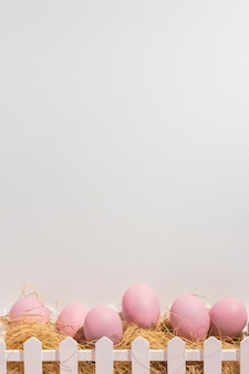 Pink easter eggs on hay in box