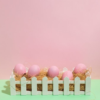 Pink easter eggs on hay on green table