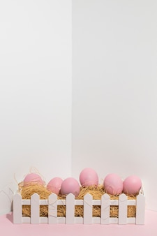 Pink easter eggs on hay in white box