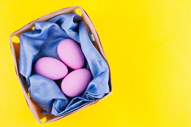 나무 상자에 분홍색 부활절 달걀입니다. 부활절 최소한의 개념. 바구니에 계란