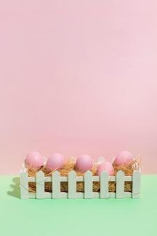 Розовые пасхальные яйца на сене в коробке на столе