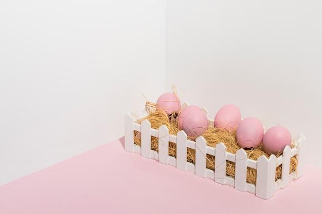 Розовые пасхальные яйца на сене на светлом столе