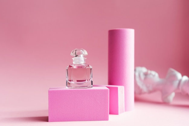 핑크색 받침대와 핑크색 배경이있는 유리 병의 핑크 오 드 퍼퓸