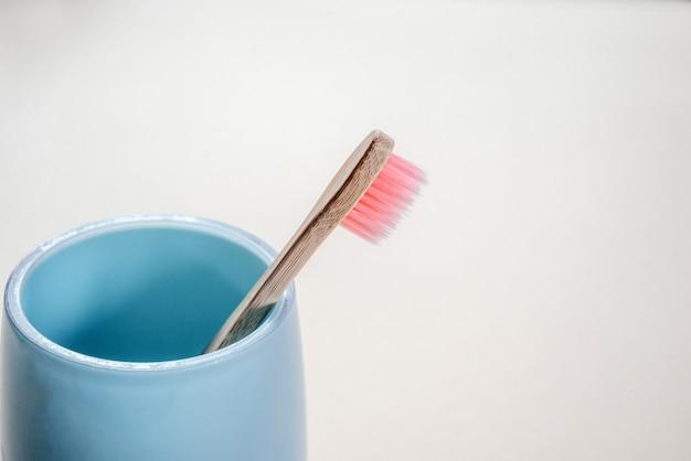 ピンクの環境にやさしい竹の歯ブラシ、青いカップのクローズアップ、コピースペースの歯科治療、ゼロウェイストのコンセプト、持続可能なライフスタイル