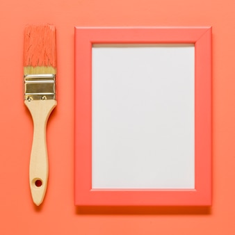 Pink empty frame with brush on colored surface