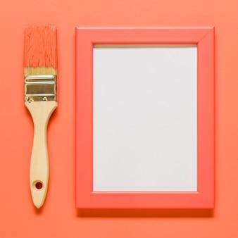 Розовая пустая рамка с кистью на цветной поверхности