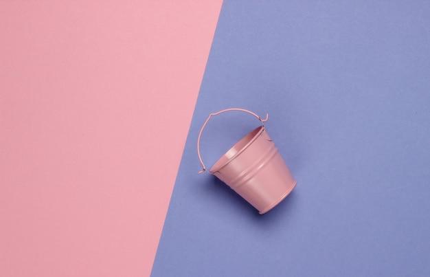 色付きのパステルカラーの背景にピンクの空のミニバケツ。ミニマリズム。トレンドカラーのコンセプト。上面図