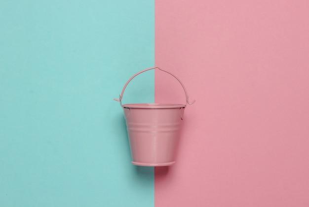 ピンクブルーのパステルカラーの背景にピンクの空のミニバケツ。ミニマリズム。トレンドカラーのコンセプト。上面図