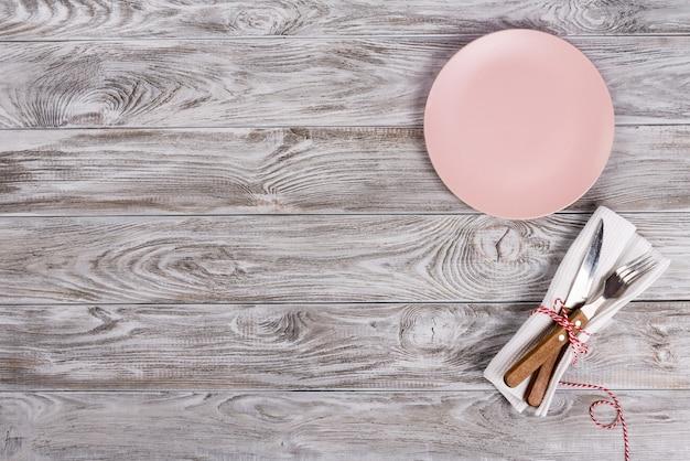 Розовая пустая тарелка и вилка и нож на деревянной предпосылке текстуры. концепция романтического ужина.