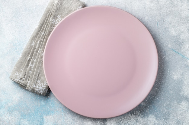 Pink empty plate with cutlery and beige towel.