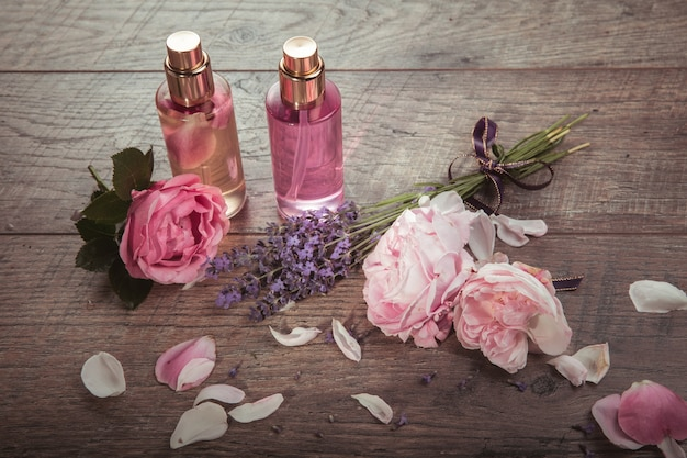 Pink english rose, lavender, organic salt and oil, spa concept on wooden background. rustic style.