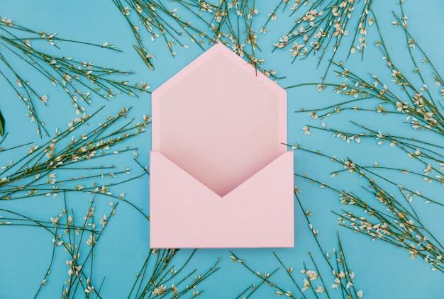 Розовый конверт и цветы на синем фоне. вид сверху