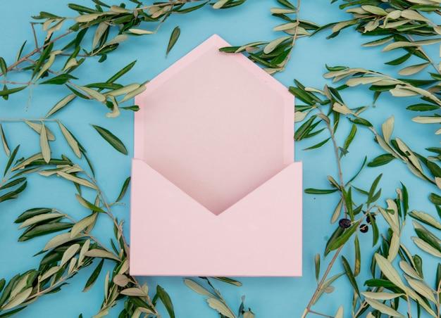 Розовый конверт и оливковые ветви на синем фоне. вид сверху