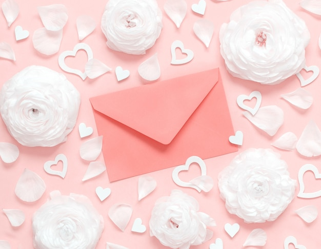 Pink envelope between cream flowers, petals and hearts on a light pink top view