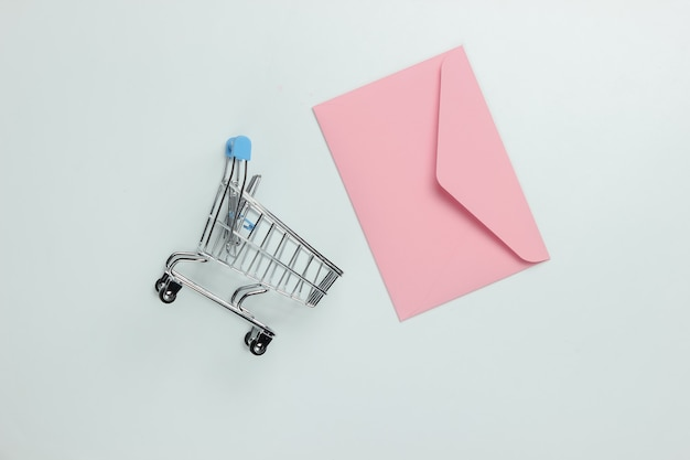 Pink envelope and shopping trolley on white background. mockup for valentines day, wedding or birthday. top view