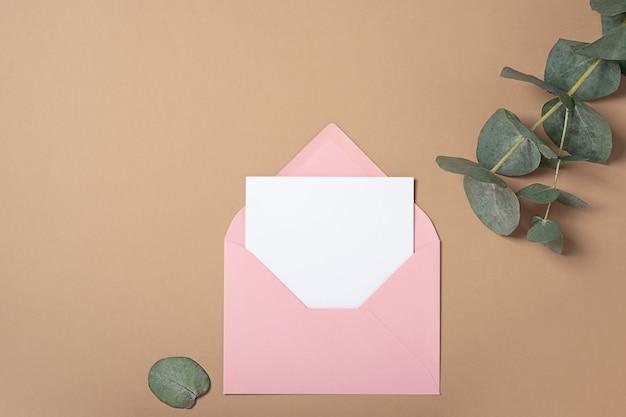 ユーカリの枝が付いているピンクの封筒の正方形の招待カードのモックアップ。コピースペース、パステルベージュの背景を持つ上面図。ブランディングと広告のためのテンプレート