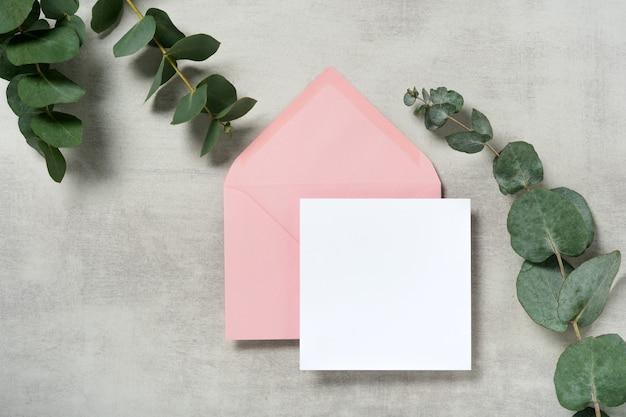 유칼립투스 분기와 핑크색 봉투 광장 초대 카드 모형
