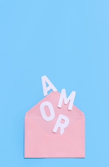Pink envelope and text amor on a light blue background top view