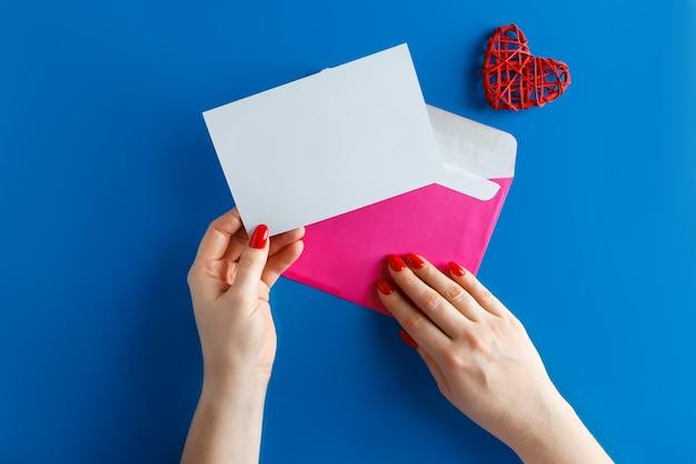 青い背景の手に空白のカードとピンクの封筒。きれいなグリーティングカードと青い背景の上のハートの封筒。バレンタインデーのデザインのコンセプト。
