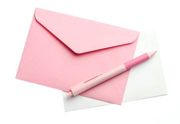 Розовый конверт с письмом и ручкой, изолированные на белом фоне.