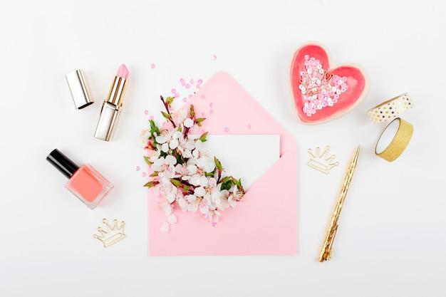 春のフラワーアレンジメントとアクセサリーが付いたピンクの封筒。フラットレイ、上面図。