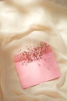 春のフラワーアレンジメントが施されたピンクの封筒。フラットレイ、上面図