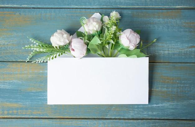 Розовый конверт с весенней цветочной композицией. плоская планировка, вид сверху.