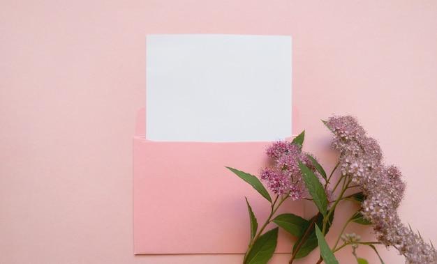 분홍색 배경에 흰색 모형 시트와 그 옆에 분홍색 꽃이 있는 분홍색 봉투. 뉴스레터 및 기타 메일 디자인용 템플릿입니다.