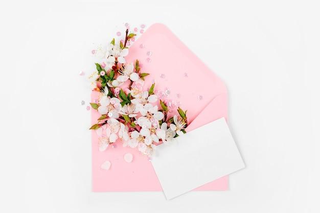 空のカードと春のフラワーアレンジメントが入ったピンクの封筒。フラットレイ、上面図。