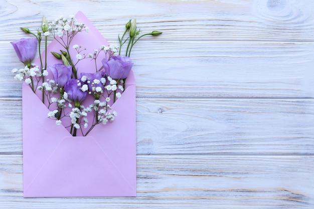 白い木製のテーブル、グリーティングカードに花模様のピンクの封筒