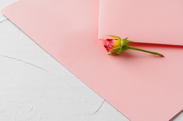 花、トップビューでピンクの封筒。ロマンチックな手紙