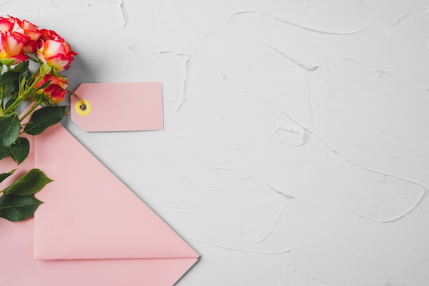 Pink envelope with flowers, top view. romantic letter