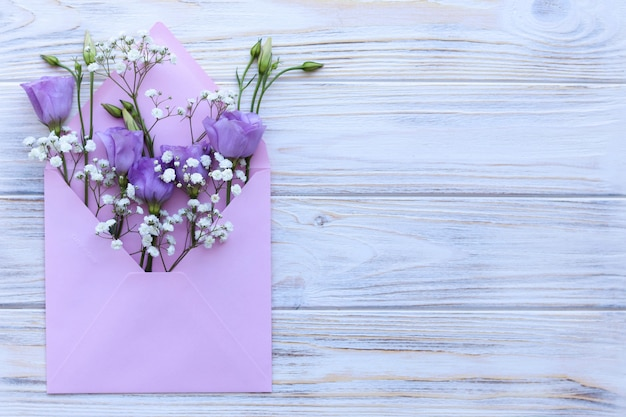 Pink envelope with flowers on a white wooden table, greeting card