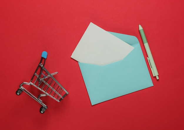 Розовый конверт с письмом и тележкой для покупок на красном фоне. мокап на день святого валентина, свадьбу или день рождения. вид сверху