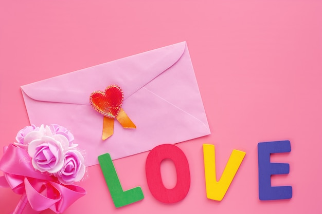 Pink envelope with red heart, flower bouquet and love word on pink background