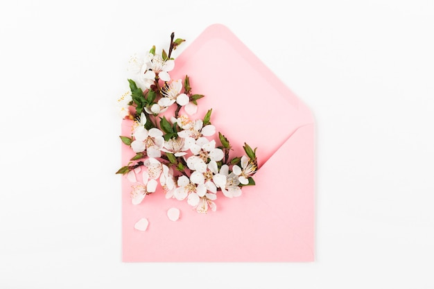 Pink envelope with a spring flower arrangement. flat lay, top view.