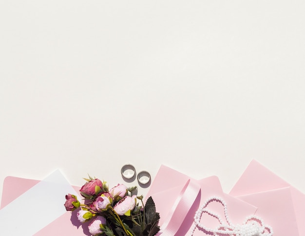 Pink envelopes next to bouquet of roses with copy space