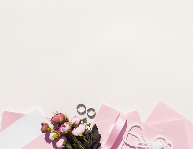 Розовые конверты рядом с букетом роз с копией пространства