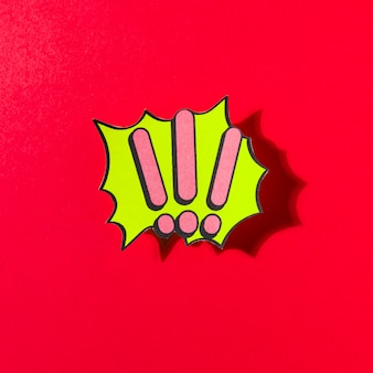 Pink exclamatory marks on green speech bubble on red backdrop