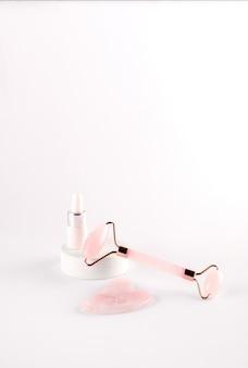 ピンクのフェイスローラーと白い背景の上に化粧品のマッサージオイルと天然石英石から作られたグアシャマッサージャー。自宅でのリフティングとトーニングトリートメント。
