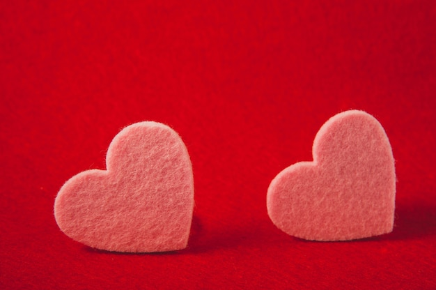 Pink felt hearts on red background, valentine's day
