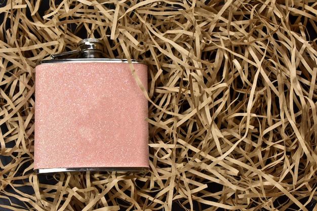 밝은 짚 배경에 분홍색 여성 플라스크