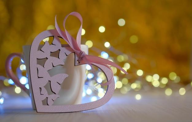 Розовое праздничное сердце на золотом фоне боке