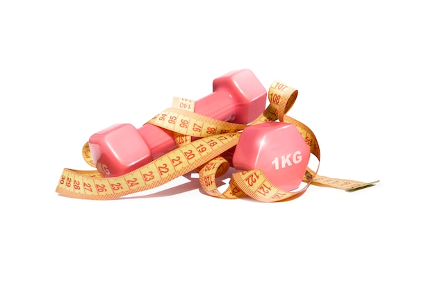 Pink fitness dumbbells and tape measure on white background