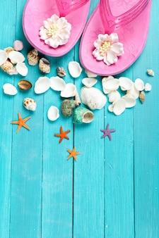 青い木の表面にピンクのビーチサンダルと貝殻