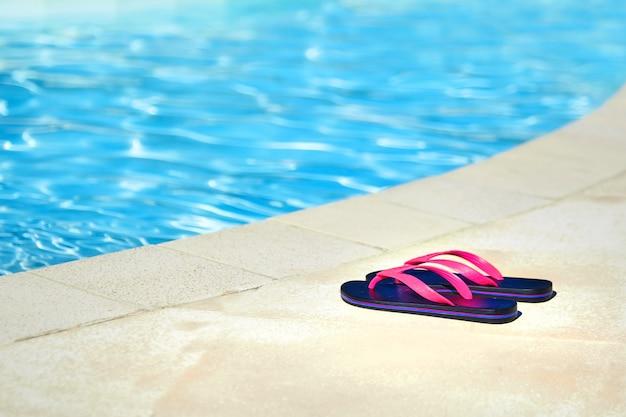 青い水のプールの近くのピンクのビーチサンダル。夏のリゾート地。ビーチシューズ