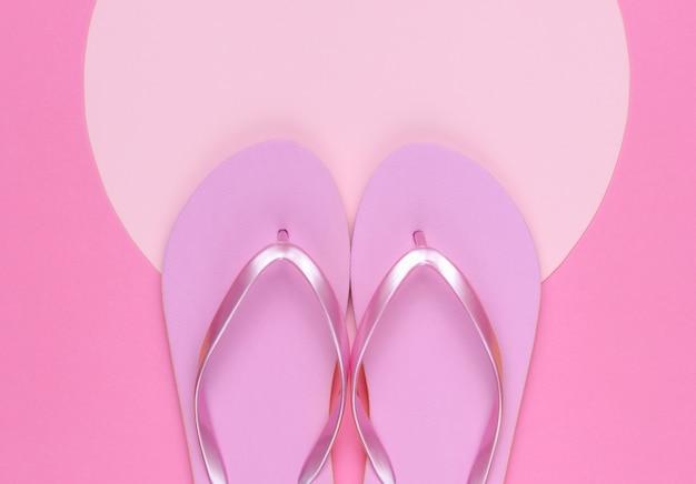 핑크색 플립플롭은 분홍색 배경에 복사 공간을 위한 분홍색 파스텔 원이 있습니다. 해변 개념에 대한 최소한의 휴가입니다. 여름 시간입니다. 평면도