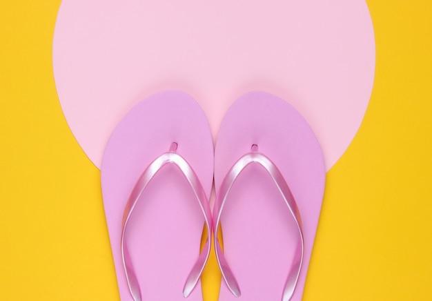 コピースペース用のピンクのパステルサークルと黄色の背景にピンクのビーチサンダル。ビーチのコンセプトでミニマルな休暇。夏時間。上面図