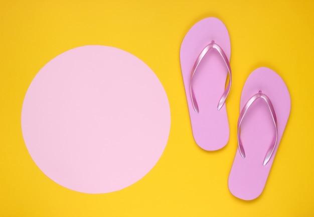 コピースペース用のピンクのパステルサークルと黄色の背景にピンクのビーチサンダル。ビーチのコンセプトでミニマルな休暇。夏時間