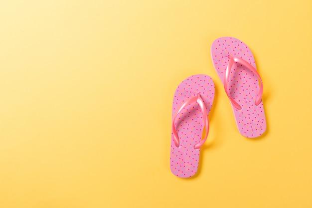 Pink flip flops on yelow.